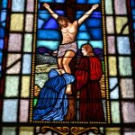 up close stain glass of jesus on the cross in the church sanctuary